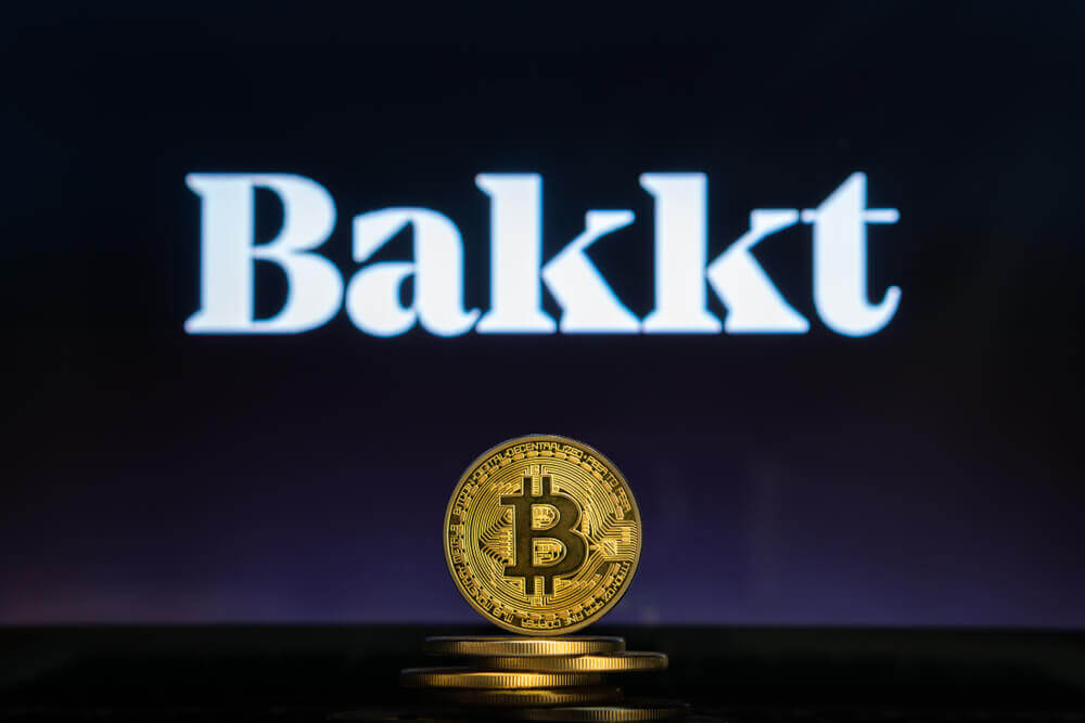 Finance Brokerage – Digital Coins: Bitcoin on a stack of coins with Bakkt logo on a laptop screen.