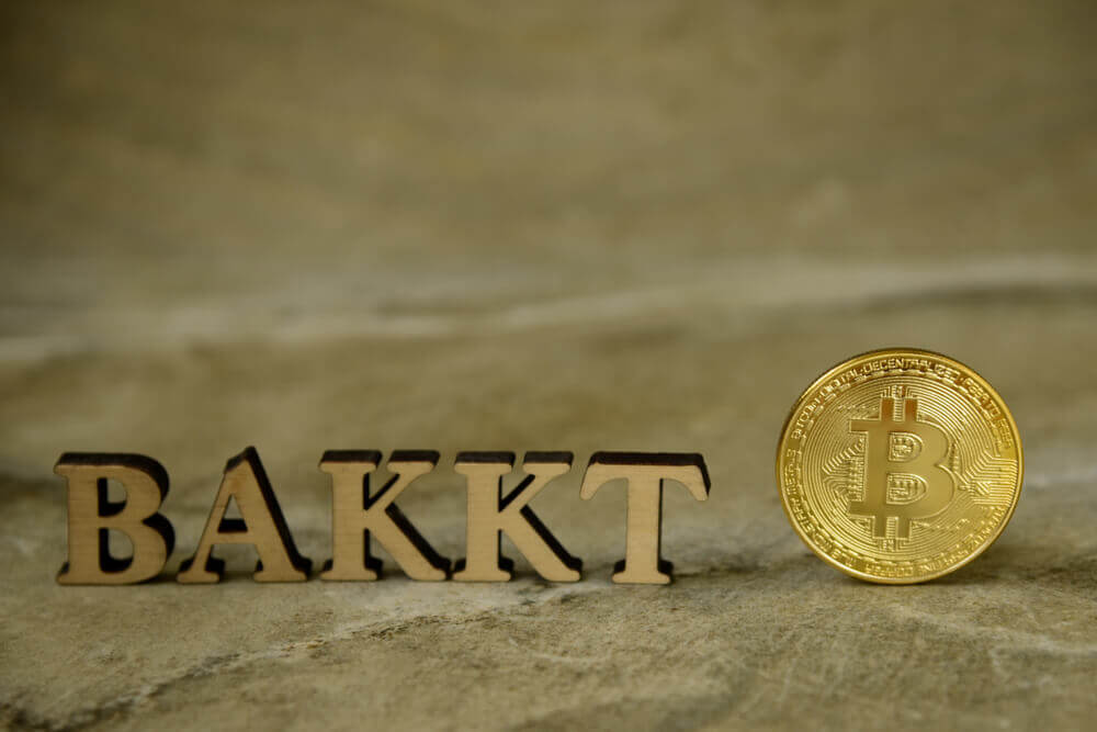 Finance Brokerage – Digital Coins: Bitcoin coin and next to wooden with BAKKT letters on stone background.