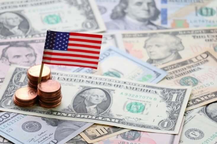 US miniature flag on top of dollar bills – financebrokerage