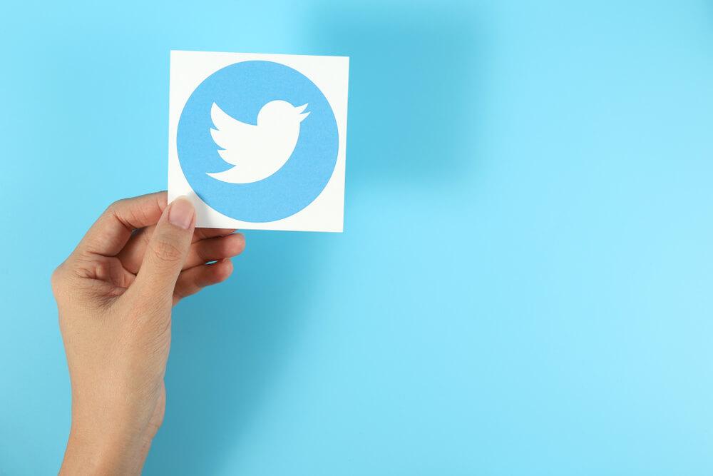 Twitter : Main tenant un logo Twitter sur fond bleu clair.