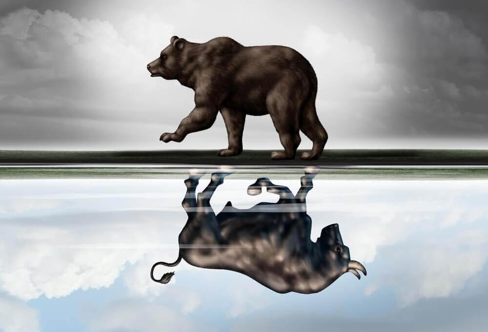 A bull walking on top of a line, a bear walking under it like a reflection.
