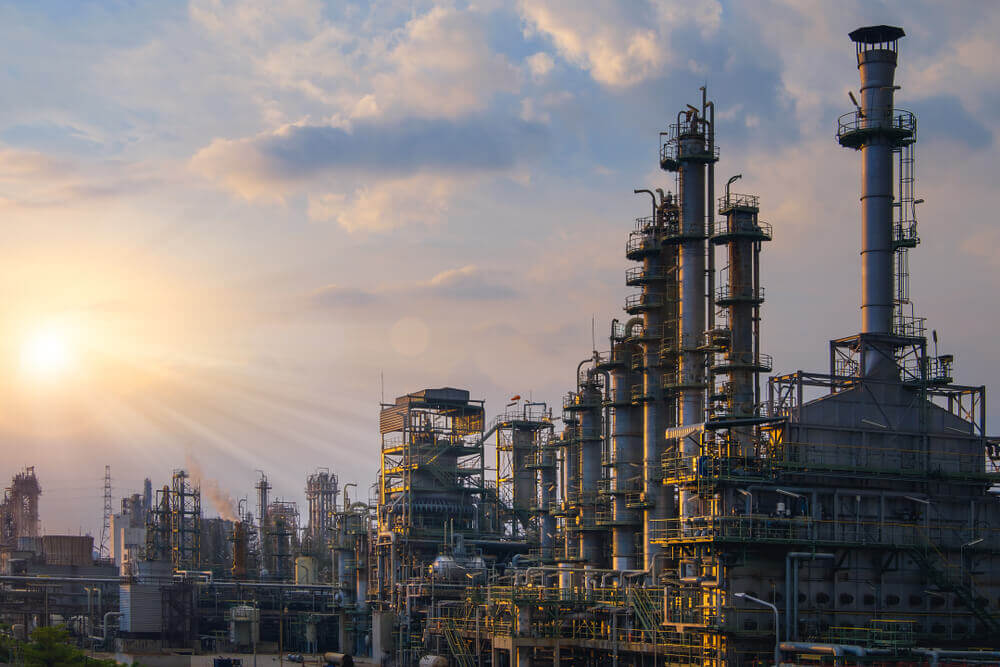 Manufacturing of petroleum industrial plant with a sunset sky background.