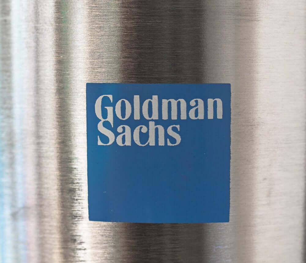 A blue logo of Goldman Sachs on a metallic convex surface.