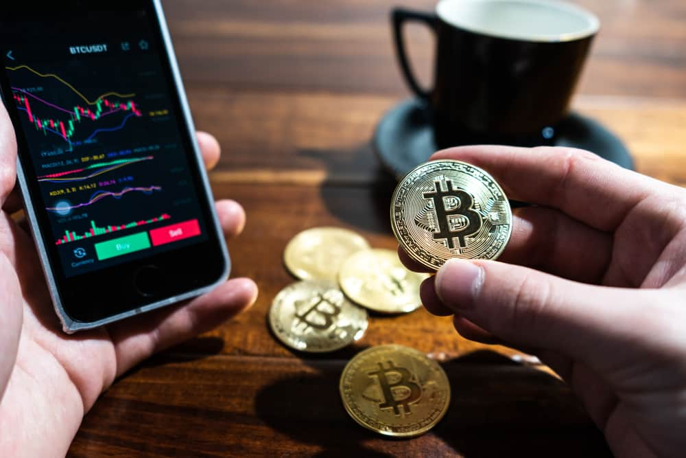 pessoa segurando bitcoin e celular